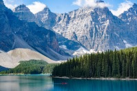 A group in a canoe takes in the blue waters of Lake Moraine.